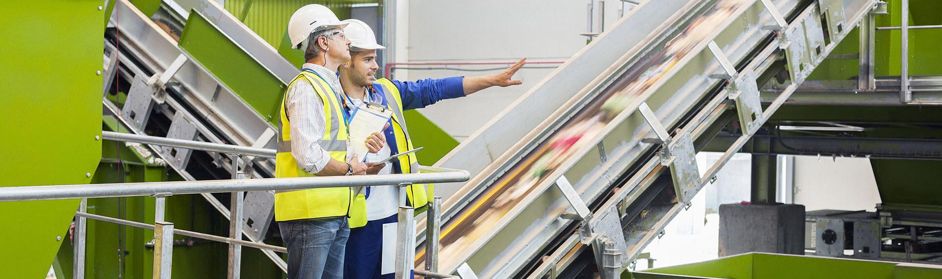 Dos personas ingenieros de GTA Ambiental con casco blanco en planta de reciclaje desarrollada por GTA Ambiental